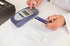 Φαρμακοποιός χρησιμοποιώντας το αριθμητικό πληκτρολόγιο και κρατώντας την πιστωτική κάρτα Στοκ εικόνα με δικαίωμα ελεύθερης χρήσης