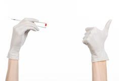 Φαρμακολογία και ιατρικό θέμα: ο γιατρός παραδίδει τσιμπιδάκια μιας τα άσπρα γαντιών εκμετάλλευσης με την κόκκινη κάψα χαπιών που στοκ εικόνες με δικαίωμα ελεύθερης χρήσης