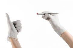 Φαρμακολογία και ιατρικό θέμα: ο γιατρός παραδίδει τσιμπιδάκια μιας τα άσπρα γαντιών εκμετάλλευσης με την κόκκινη κάψα χαπιών που στοκ φωτογραφία