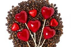 φασόλια καφέ, καραμέλες σοκολάτας και διακοσμητικές καρδιές στα ραβδιά Στοκ Εικόνα