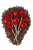 φασόλια καφέ, καραμέλες σοκολάτας και διακοσμητικές καρδιές στα ραβδιά στοκ εικόνες