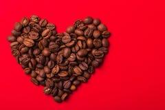 Φασόλια καφέ, μορφή καρδιών, κόκκινο υπόβαθρο Κύμα χρώματος valentin Στοκ εικόνα με δικαίωμα ελεύθερης χρήσης