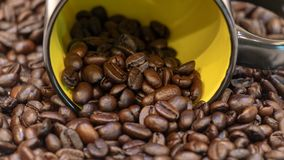 Φασόλια καφέ που ανατρέπουν από το κίτρινο κεραμικό φλυτζάνι Στοκ εικόνες με δικαίωμα ελεύθερης χρήσης