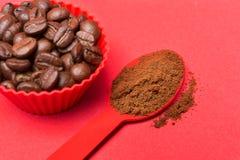 Φασόλια καφέ σε ένα κόκκινο εμπορευματοκιβώτιο σε ένα κόκκινο υπόβαθρο, κονιοποιημένος επίγειος καφές σε ένα κόκκινο κουτάλι στοκ φωτογραφίες