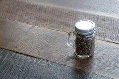 Φασόλια καφέ στα μπουκάλια γυαλιού με το παλαιό ξύλινο πάτωμα στοκ εικόνα