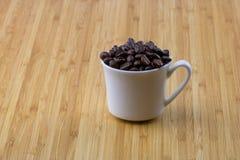 Φασόλια καφέ στην κούπα espresso Στοκ Φωτογραφία