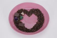 Φασόλια καφέ στη μορφή μιας καρδιάς με τα κομμάτια της σοκολάτας Στοκ Εικόνες