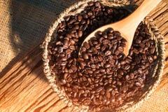 Φασόλια καφέ στο ξύλινο κουτάλι πέρα από το καλάθι στοκ εικόνες