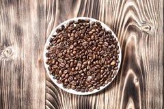 Φασόλια καφέ φρέσκα που ψήνει στο στρογγυλό κύπελλο σε έναν ξύλινο πίνακα Στοκ εικόνα με δικαίωμα ελεύθερης χρήσης