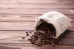 Φασόλια καφέ burlap στο σάκο στον καφετή πίνακα στοκ φωτογραφίες