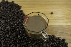 Φασόλι καφέ και φλυτζάνι στον ξύλινο φραγμό Στοκ φωτογραφία με δικαίωμα ελεύθερης χρήσης