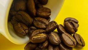 Φασόλι καφέ που ρέει από το άσπρο φλυτζάνι καφέ στο κίτρινο υπόβαθρο Στοκ Φωτογραφία