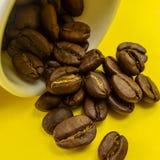 Φασόλι καφέ που ρέει από το άσπρο φλυτζάνι καφέ στο κίτρινο υπόβαθρο Στοκ φωτογραφίες με δικαίωμα ελεύθερης χρήσης