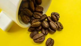 Φασόλι καφέ που ρέει από το άσπρο φλυτζάνι καφέ στο κίτρινο υπόβαθρο Στοκ εικόνα με δικαίωμα ελεύθερης χρήσης