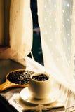 Φασόλι καφέ σε ένα φλυτζάνι, παράθυρο Στοκ φωτογραφία με δικαίωμα ελεύθερης χρήσης