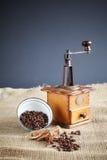 Φασόλια καφέ και ένας παλαιός μύλος καφέ στο υπόβαθρο γιούτας Στοκ Εικόνες