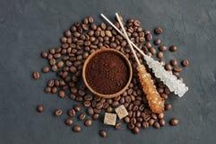 Φασόλια καφέ και επίγειος καφές σε μια ξύλινη ζάχαρη κύπελλων και καλάμων Στοκ Εικόνες