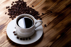 Φασόλια καφέ και καφές στο άσπρο φλυτζάνι στον ξύλινο πίνακα εκλεκτικός Στοκ φωτογραφία με δικαίωμα ελεύθερης χρήσης