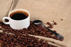Φασόλια καφέ και κουταλάκι του γλυκού του επίγειου καφέ με ένα φλιτζάνι του καφέ Στοκ φωτογραφία με δικαίωμα ελεύθερης χρήσης