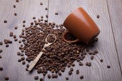 Φασόλια καφέ και φλυτζάνι καφέ στην ξύλινη επιφάνεια Στοκ Εικόνες