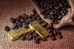 Φασόλια καφέ και χρυσή ράβδος sackcloth στην τσάντα στο ξύλινο backgro Στοκ φωτογραφία με δικαίωμα ελεύθερης χρήσης