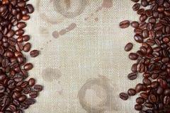 Φασόλια καφέ και burlap με τους λεκέδες καφέ Στοκ Φωτογραφίες