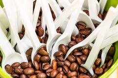 Φασόλια καφέ με τα άσπρα πλαστικά κουτάλια Στοκ φωτογραφία με δικαίωμα ελεύθερης χρήσης