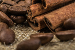 Φασόλια καφέ με τα ραβδιά κανέλας στο κλωστοϋφαντουργικό προϊόν σάκων Στοκ Φωτογραφίες