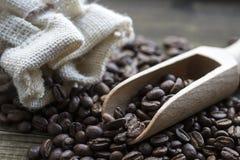 Φασόλια καφέ με την ξύλινη τσάντα σεσουλών και λινού στον ξύλινο πίνακα Στοκ Εικόνα