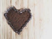 Φασόλια καφέ μορφής καρδιών και επίγειος καφές με το διάστημα αντιγράφων Στοκ Εικόνα