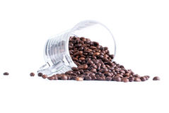 Φασόλια καφέ που ανατρέπονται από ένα φλυτζάνι γυαλιού που απομονώνεται στο άσπρο backgrou Στοκ Φωτογραφία