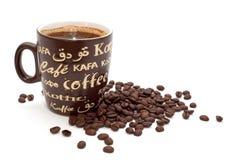 Φασόλια καφέ που ανατρέπονται περίπου ένα φλιτζάνι του καφέ Στοκ Εικόνες