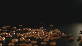 Φασόλια καφέ - που πέφτουν ένας μακρο πυροβολισμός 96 fps των φασολιών καφέ που αφορούν τη μαύρη επιφάνεια Ένας όμορφος γενικός π απόθεμα βίντεο