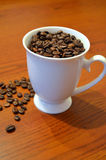 Φασόλια καφέ που χύνονται σε ένα άσπρο φλυτζάνι Στοκ Φωτογραφίες