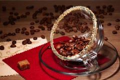 Φασόλια καφέ σε ένα διαφανές φλυτζάνι και μια καφετιά ζάχαρη κομματιών Στοκ Εικόνες