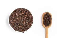Φασόλια καφέ σε ένα κύπελλο και ένα κουτάλι Στοκ εικόνες με δικαίωμα ελεύθερης χρήσης
