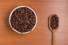 Φασόλια καφέ σε ένα κύπελλο και ένα κουτάλι Arabica Coffea Στοκ εικόνες με δικαίωμα ελεύθερης χρήσης