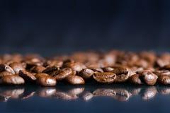 Φασόλια καφέ σε ένα μαύρο υπόβαθρο καφές φασολιών ακατέργασ Κοκκιώδες προϊόν ποτό ζεστό κλείστε επάνω συγκομιδή Φυσική ανασκόπηση Στοκ Φωτογραφίες