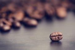 Φασόλια καφέ σε ένα μαύρο υπόβαθρο Φασόλια καφέ μετεωρισμού Κοκκιώδες προϊόν ποτό ζεστό κλείστε επάνω συγκομιδή Φυσική ανασκόπηση Στοκ Φωτογραφία