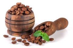 Φασόλια καφέ σε ένα ξύλινο κύπελλο με τη σέσουλα που απομονώνεται στο άσπρο υπόβαθρο Στοκ Εικόνες