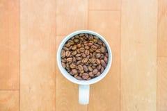Φασόλια καφέ σε ένα φλυτζάνι Στοκ Φωτογραφία