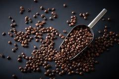 Φασόλια καφέ σε μια σέσουλα σε ένα μαύρο υπόβαθρο Στοκ Εικόνες