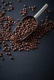 Φασόλια καφέ σε μια σέσουλα σε ένα μαύρο υπόβαθρο Στοκ Εικόνα