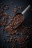 Φασόλια καφέ σε μια σέσουλα σε ένα μαύρο υπόβαθρο Στοκ εικόνα με δικαίωμα ελεύθερης χρήσης