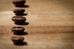 Φασόλια καφέ σε μια σειρά στο ξύλο Στοκ φωτογραφίες με δικαίωμα ελεύθερης χρήσης