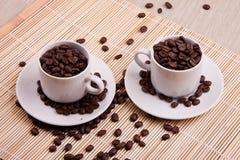 φασόλια καφέ στα φλυτζάνια καφέ Στοκ Εικόνες