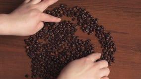 Φασόλια καφέ στον πίνακα με μορφή μιας καρδιάς απόθεμα βίντεο