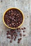 Φασόλια καφέ στο κύπελλο στο ξύλινο υπόβαθρο Στοκ Εικόνες