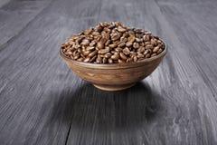 Φασόλια καφέ στο κύπελλο στο ξύλινο υπόβαθρο Στοκ Εικόνα