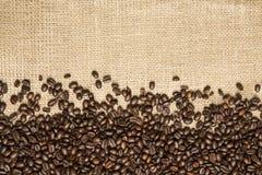 Φασόλια καφέ στο υπόβαθρο των υφασμάτων γιούτας Στοκ φωτογραφία με δικαίωμα ελεύθερης χρήσης